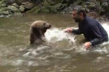 土耳其胆大男子与灰熊在溪水中戏水玩耍做出过分亲密、危险动作